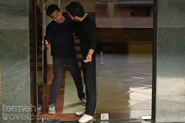 two men asking the other to go through the door first, Iranian politeness is everywhere - Termeh Travel